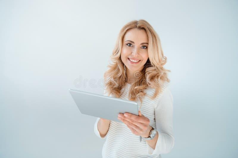 Härlig blond kvinna som använder den digitala minnestavlan på grå färger fotografering för bildbyråer