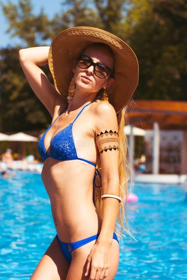 Härlig blond kvinna som bär en hatt och solglasögon som tycker om th arkivfoton