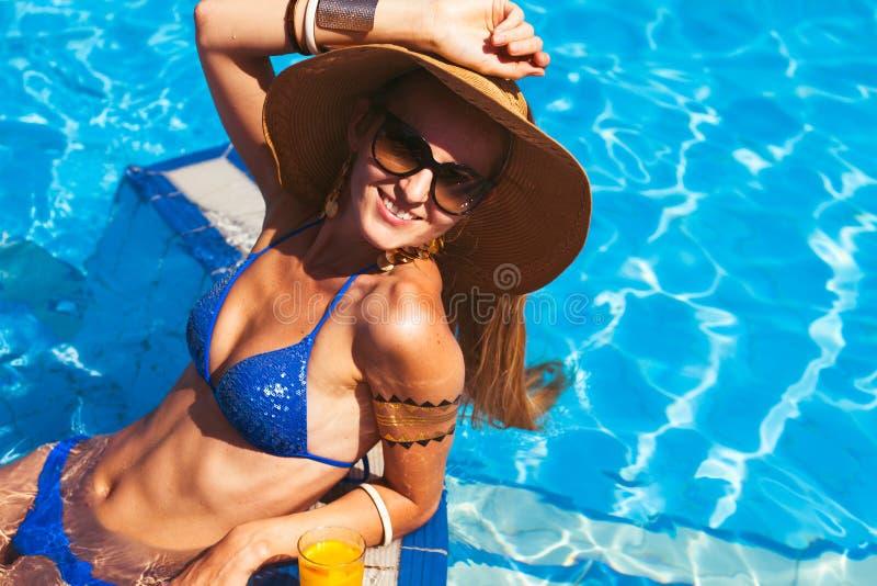 Härlig blond kvinna som bär en hatt och solglasögon som tycker om th fotografering för bildbyråer