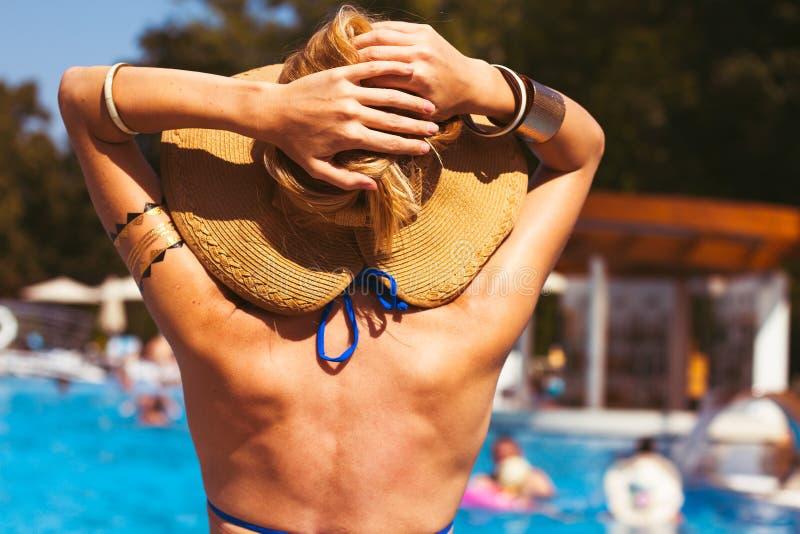 Härlig blond kvinna som bär en hatt och solglasögon som tycker om th royaltyfri bild