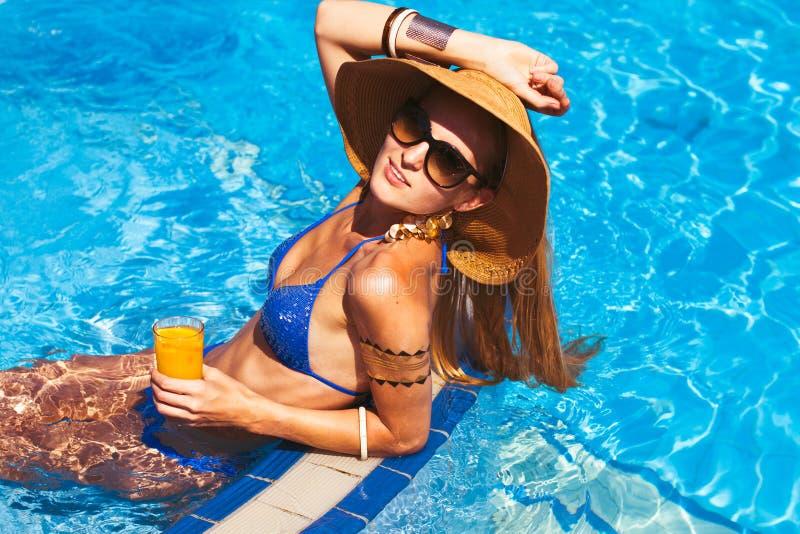 Härlig blond kvinna som bär en hatt och solglasögon som tycker om th royaltyfria foton