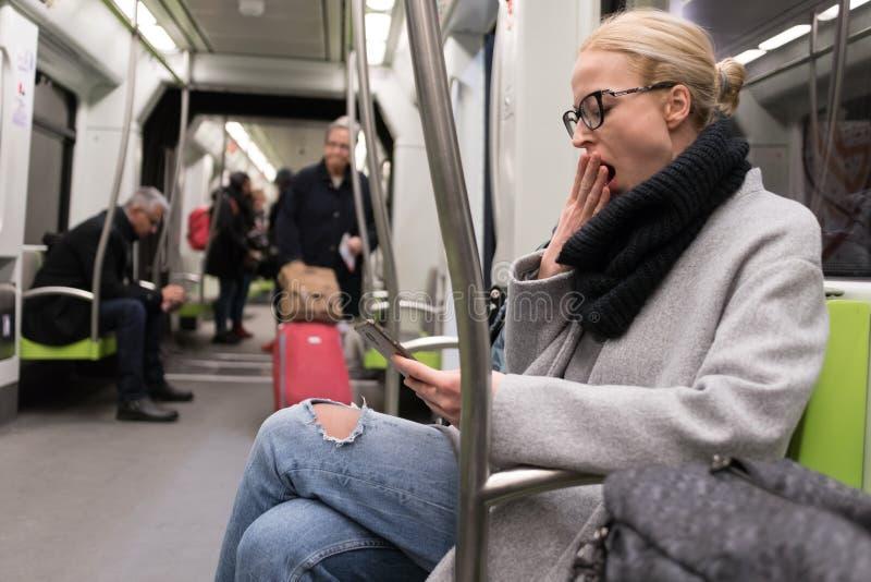 Härlig blond kvinna som gäspar, medan läsa på telefonen som reser med tunnelbanan offentlig transport royaltyfri foto