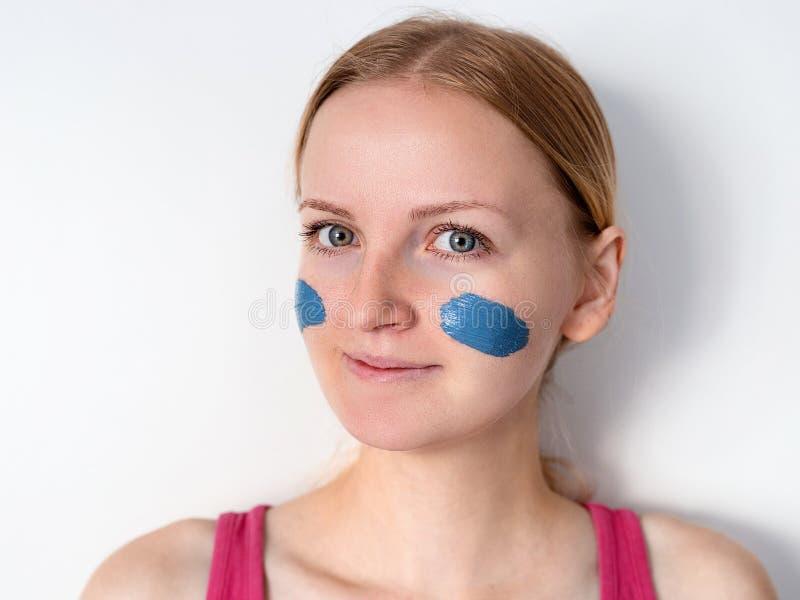 Härlig blond kvinna som har den ansikts- maskeringen för blå lera att applicera vid kosmetologen flickan med en maskering på kind arkivbilder