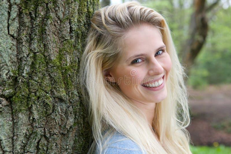 Härlig blond kvinna som ler i skogen arkivbild