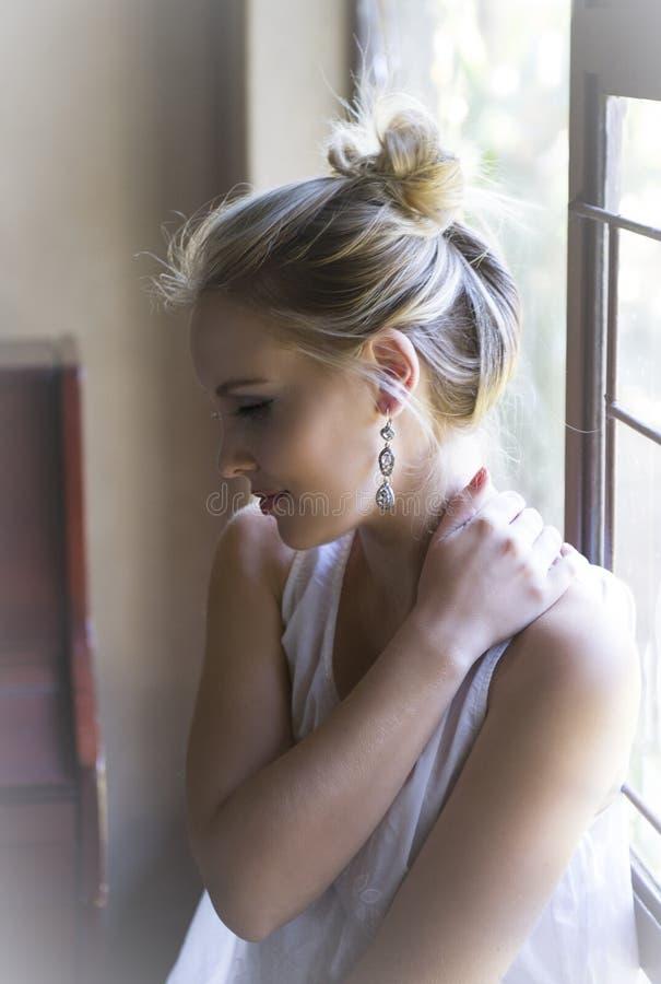 Härlig blond kvinna som placeras bredvid fönster i mjukt naturligt ljus arkivbild