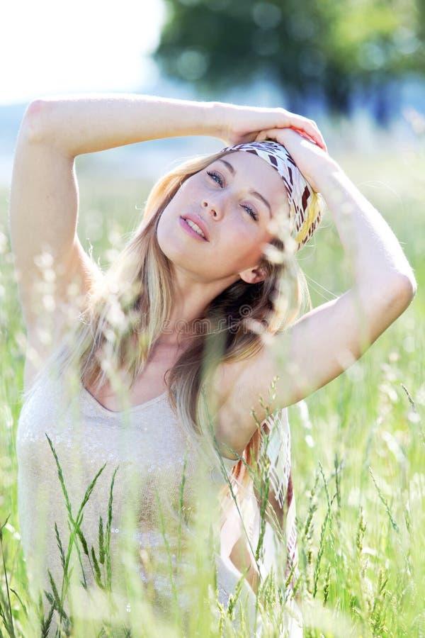 Härlig blond kvinna som poserar i äng royaltyfri bild
