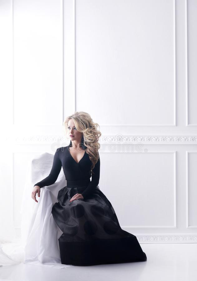 Härlig blond kvinna som poserar i en svart klänning Flickasammanträde på fåtöljen i retro inre royaltyfria foton