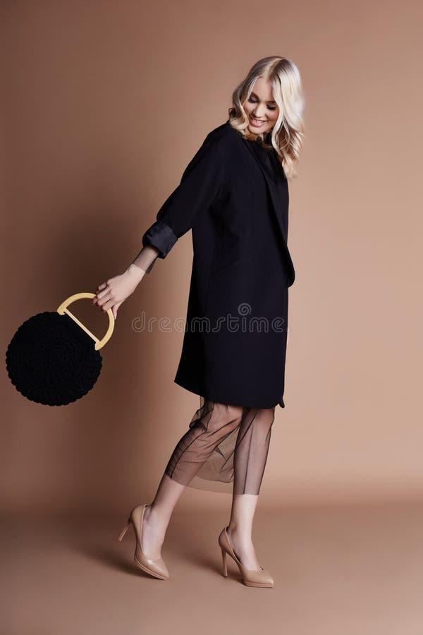 Härlig blond kvinna som poserar i ett svart lag med påsen på en beige bakgrund Modeshowkläder, kvinna med det perfekta diagramet fotografering för bildbyråer