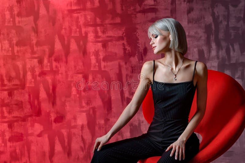 Härlig blond kvinna som poserar på en röd bakgrund i svarta overaller valentin för dag s Mall för den säsongsbetonade feriedesign royaltyfri bild