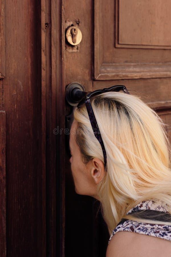Härlig blond kvinna som ser till och med nyckelhålet på en gammal trädörr royaltyfri foto
