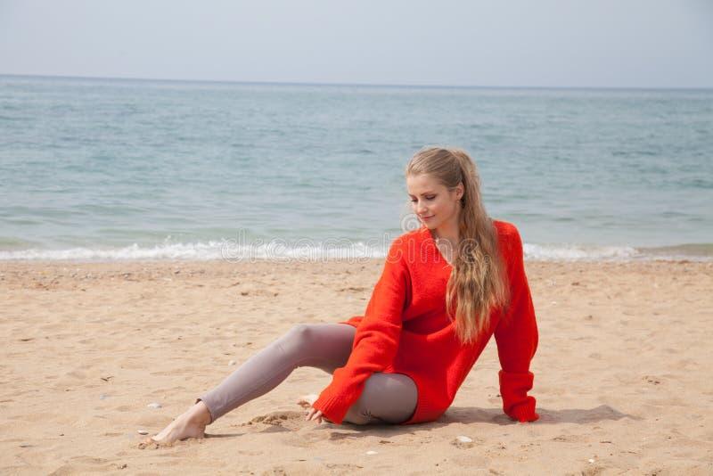 Härlig blond kvinna som sitter på stranden i förkylningen för sand en fotografering för bildbyråer