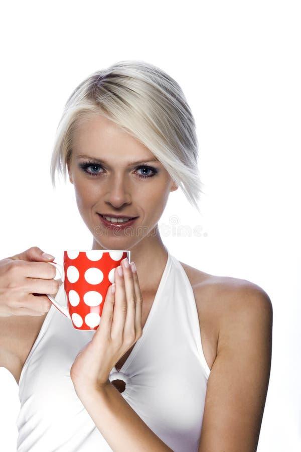 Härlig blond kvinna som tycker om en råna av kaffe arkivbild