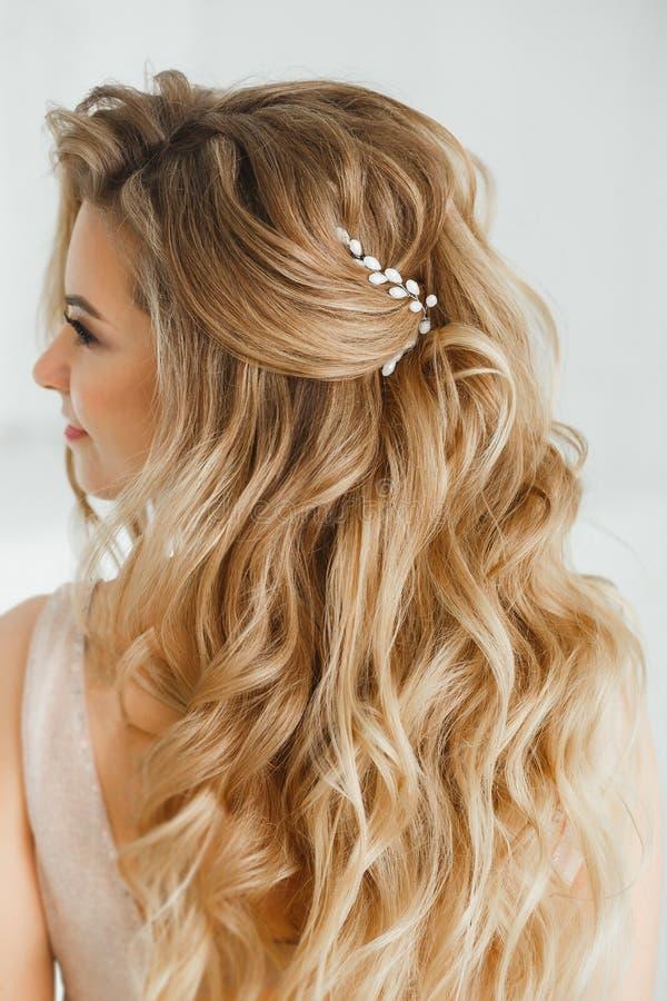 Härlig blond kvinna som visar hennes perfekta grekiska frisyr och purpurfärgade kulöra kristallörhängen med pärlor i beiga royaltyfria foton
