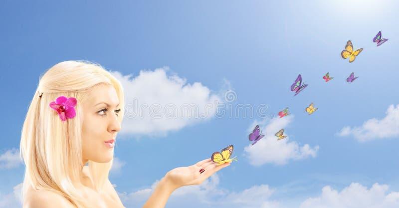 Härlig blond kvinnlig med många fjärilar på hennes hand, agains royaltyfria foton