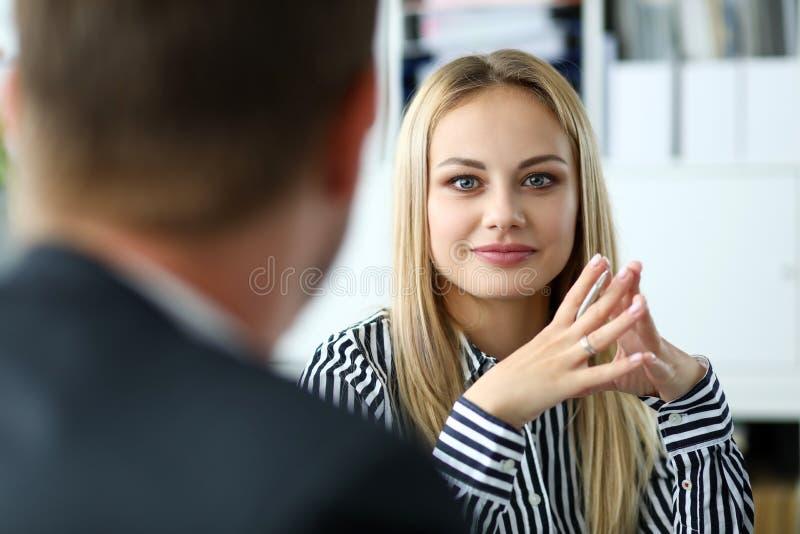 Härlig blond kvinnlig person som sitter på arbetsplatsståenden arkivfoto
