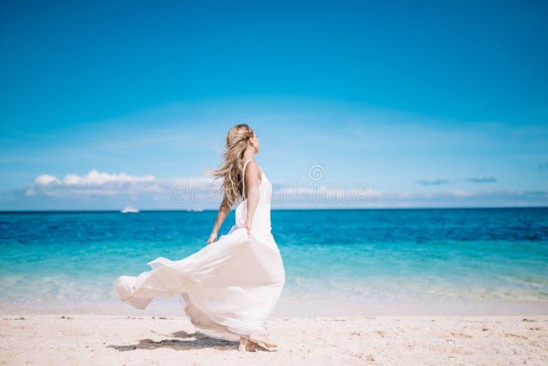 Härlig blond lång hårbrud i lång vit klänningspring på den vita sandstranden Tropiskt turquoishav på bakgrunden arkivfoton