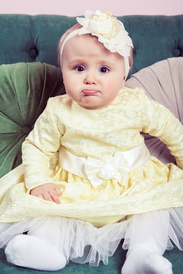 Härlig blond liten flicka med den gula klänningen och blomman på hennes huvud fotografering för bildbyråer