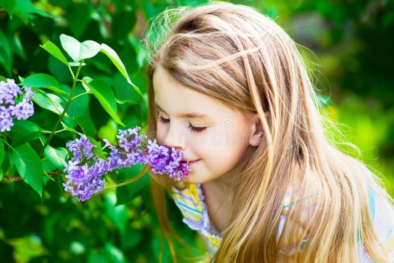 Härlig blond liten flicka med långt hår som luktar blomman arkivfoto