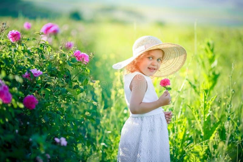 Härlig blond liten flickainnehavblomma och händer och le fotografering för bildbyråer
