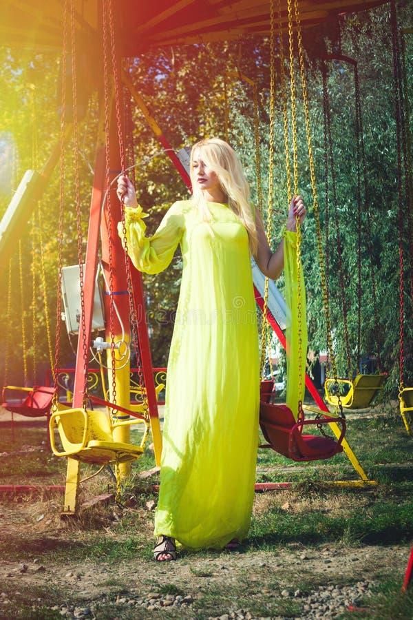 Härlig blond modekvinna i lång elegant gul klänningställning, genom att flyga karusell i sandalsommar för hög häl arkivbild