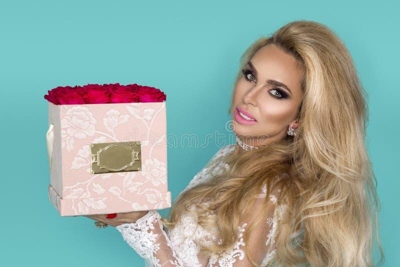 Härlig blond modell i den eleganta klänningen som rymmer en bukett av rosor, blommaask Valentin och födelsedaggåva på en blå bakg arkivfoton