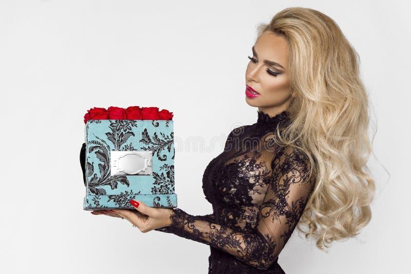 Härlig blond modell i den eleganta långa klänningen som rymmer en närvarande ask med rosor royaltyfria foton