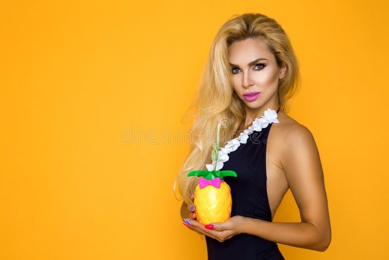 Härlig blond modell i en bikini som rymmer en ananasdrink royaltyfria foton