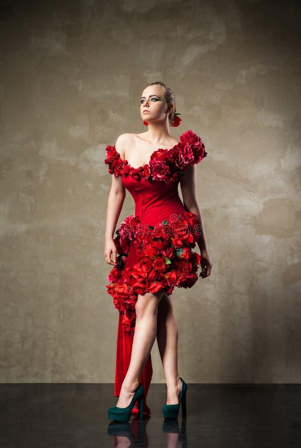 Härlig blond modell i röd blom- klänning royaltyfria foton