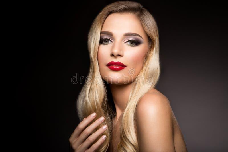 Härlig blond modellflicka med långt lockigt hår Krabb krullning för frisyr röda kanter royaltyfri fotografi