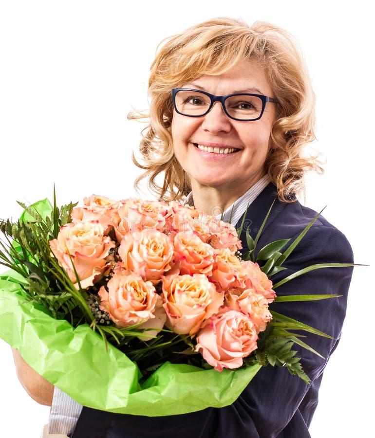 Härlig blond mogen kvinna med av rosor fotografering för bildbyråer