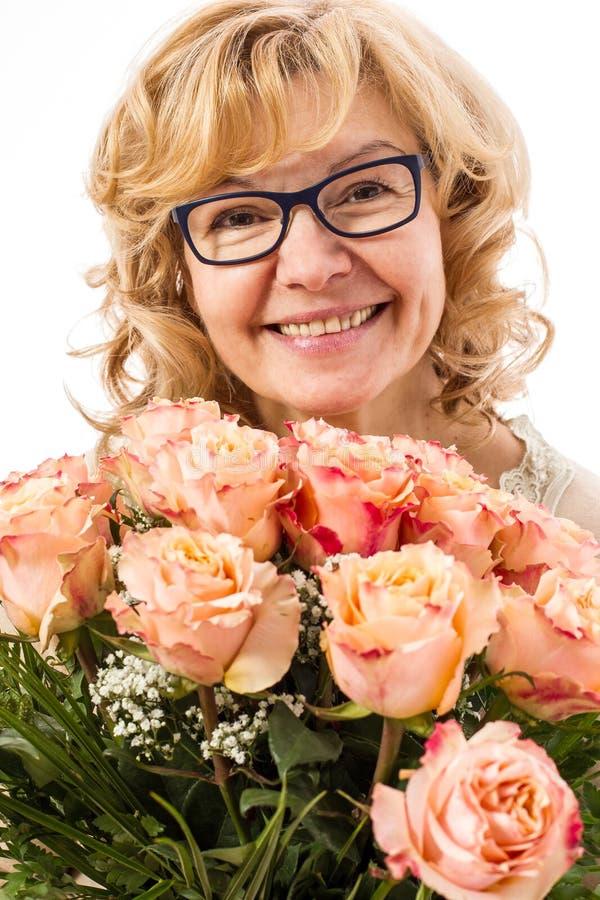 Härlig blond mogen kvinna med rosor arkivbild
