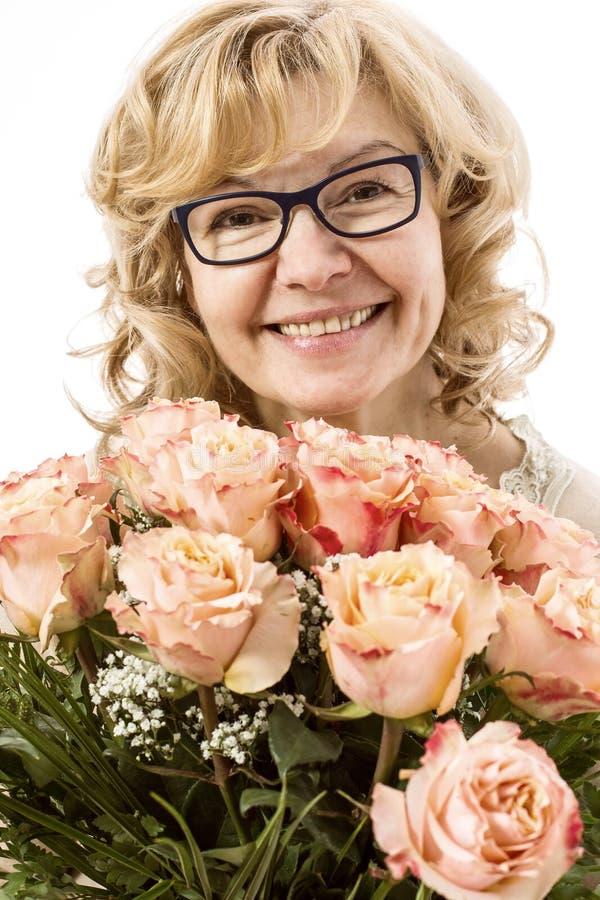 Härlig blond mogen kvinna med rosor royaltyfri bild