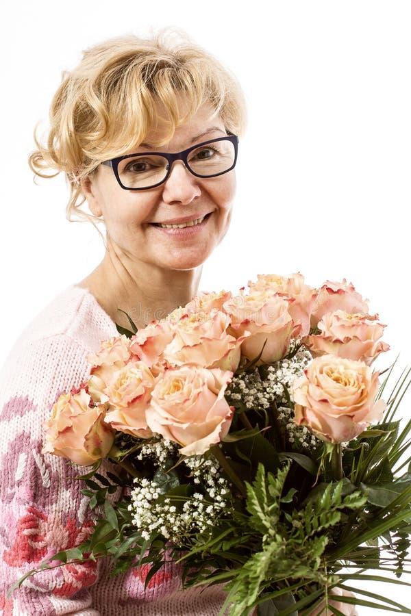 Härlig blond mogen kvinna med rosor arkivbilder