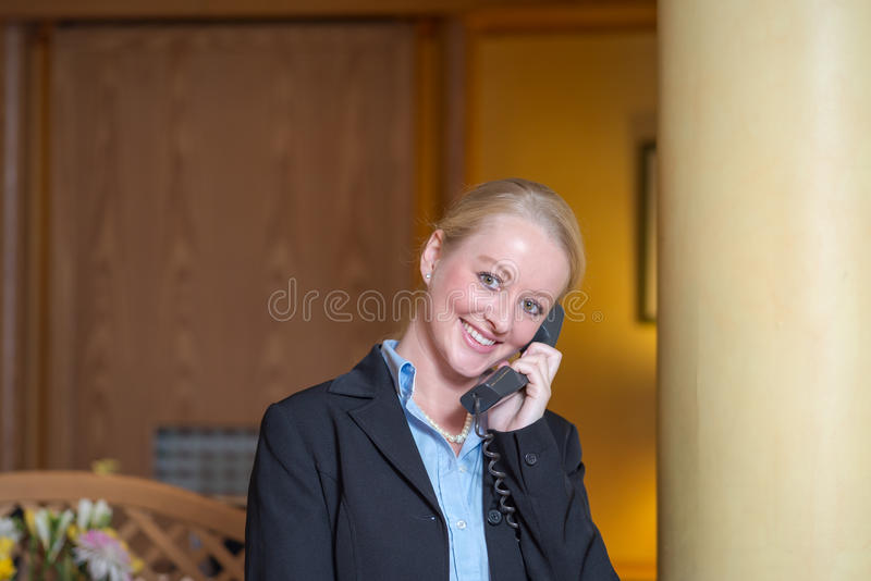 Härlig blond receptionist som svarar en telefon royaltyfri fotografi