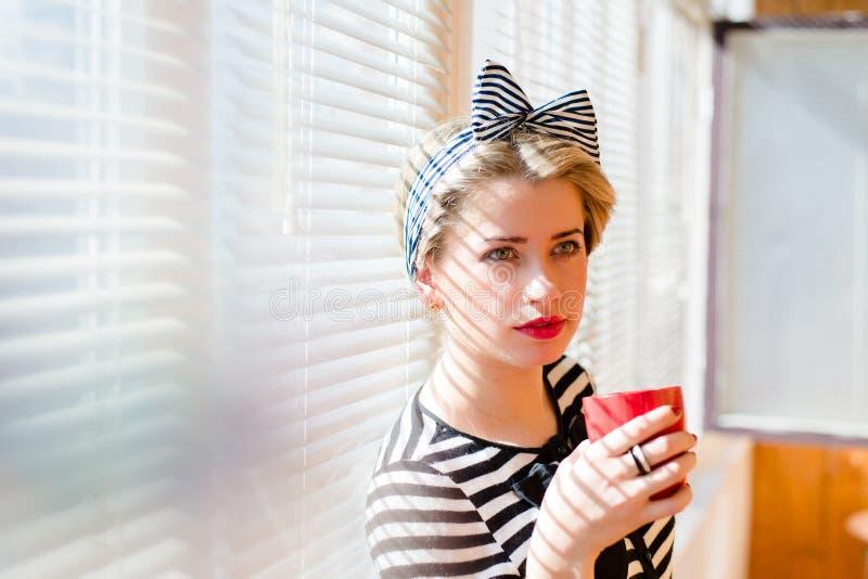 Härlig blond rolig utvikningsbrudkvinna som hemma dricker kaffe arkivfoton