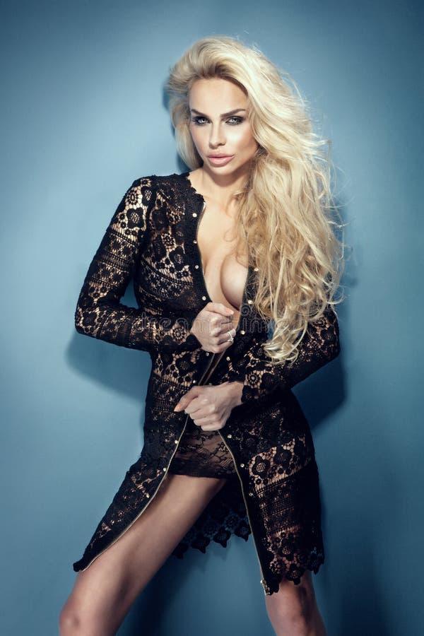 Trendig blond sexig kvinna som ha på sig svart posera för klänning. royaltyfria bilder