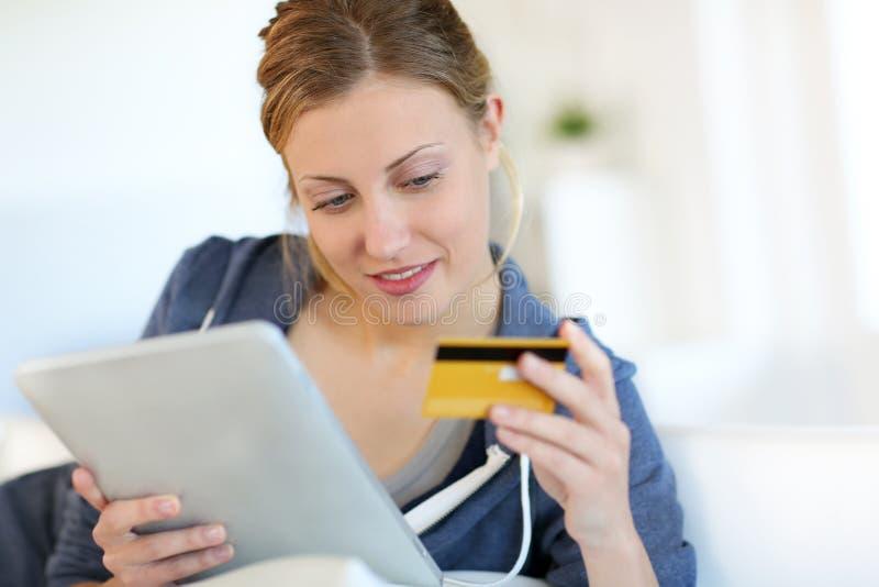 Härlig blond shopping för ung kvinna på internet royaltyfri foto