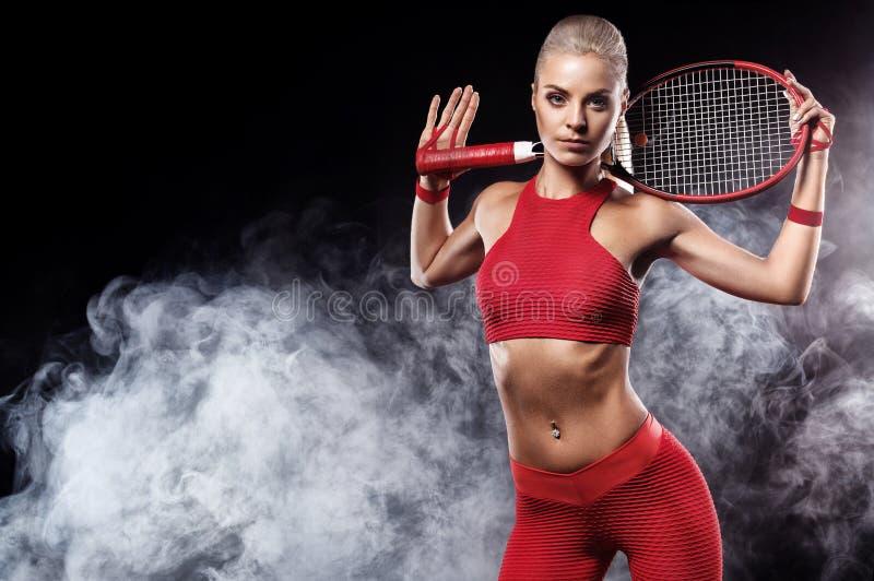 Härlig blond sportkvinnatennisspelare med racket i röd dräkt royaltyfri bild