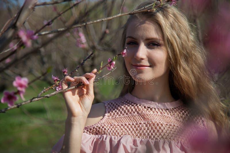 Härlig blond stående för trendig kvinna på en vit bakgrund arkivfoto