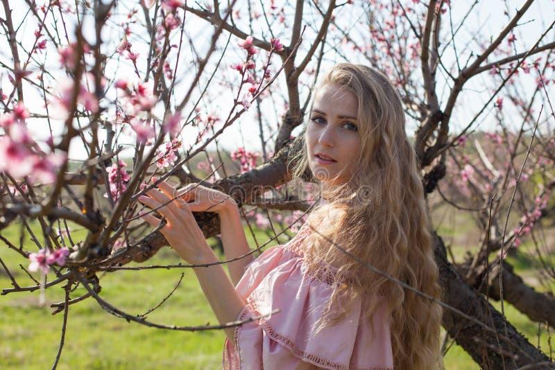 Härlig blond stående för trendig kvinna på en vit bakgrund arkivfoton