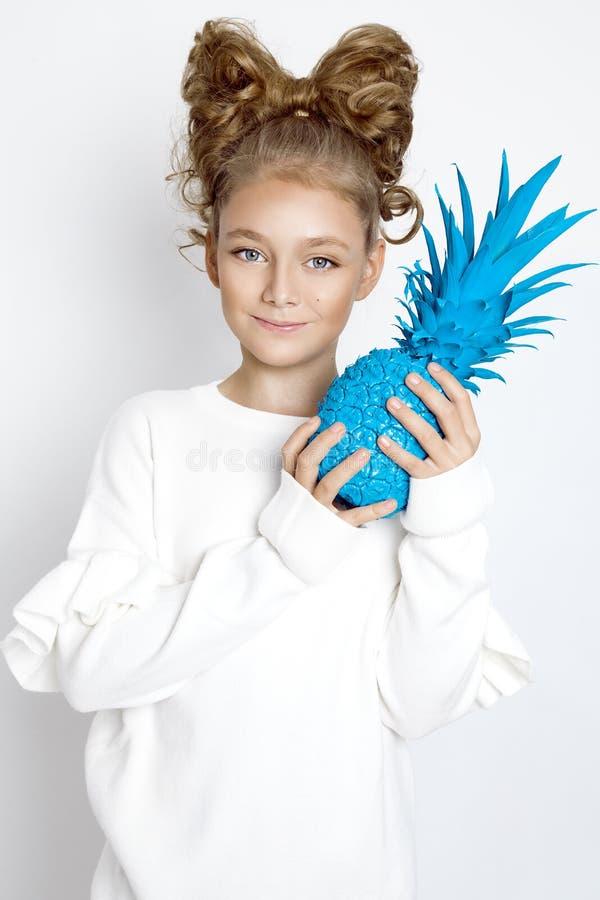 Härlig blond ung flicka med pilbågen från hår Skönhet och glad flicka, henne som rymmer färgrika frukter royaltyfria bilder