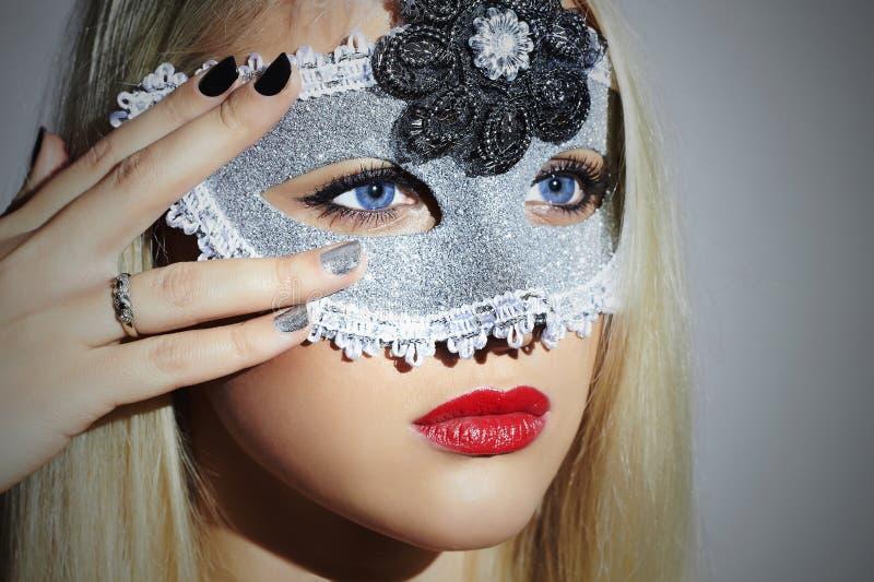 Härlig blond ung kvinna i karnevalmaskering maskerad röda isolerade kanter för bakgrundsskönhetblack flicka manicure royaltyfri foto