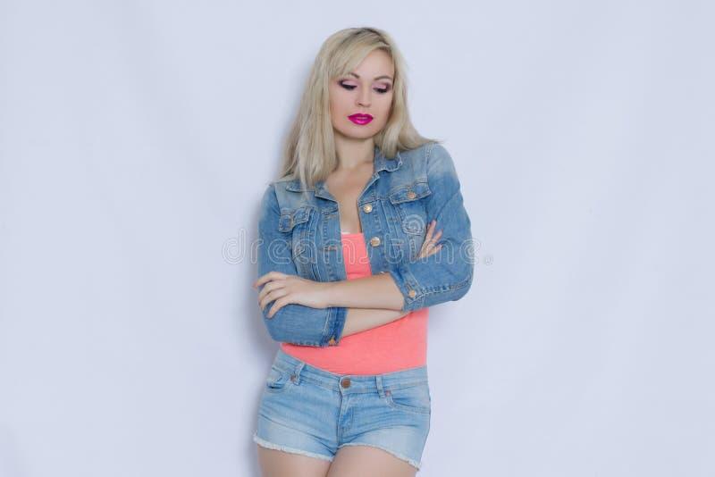 Härlig blond ung kvinna i rosa ärmlös tröja och jeansdräkt royaltyfri bild