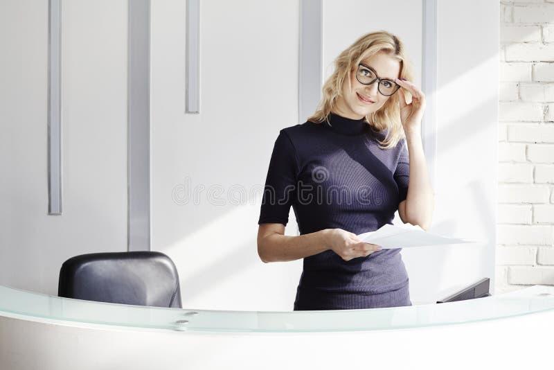 Härlig blond vänlig kvinna bak mottagandeskrivbordet, administratör som talar vid telefonen Solsken i modernt kontor arkivfoton