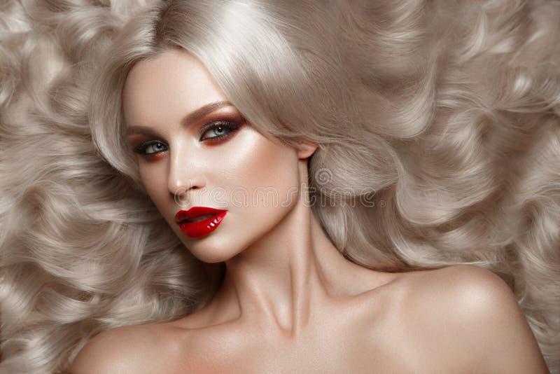 Härlig blondin i ett Hollywood sätt med krullning, naturlig makeup och röda kanter Skönhetframsida och hår arkivbilder