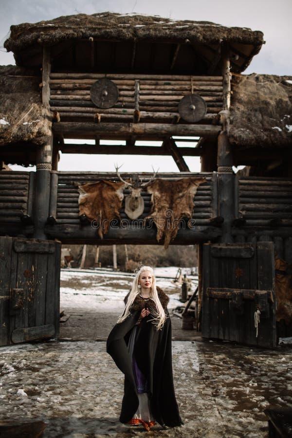 Härlig blondin iklädda Viking en svart kappa royaltyfri bild