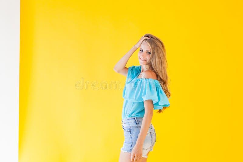 Härlig blondin med blåa ögon som poserar på en gul bakgrund royaltyfri bild