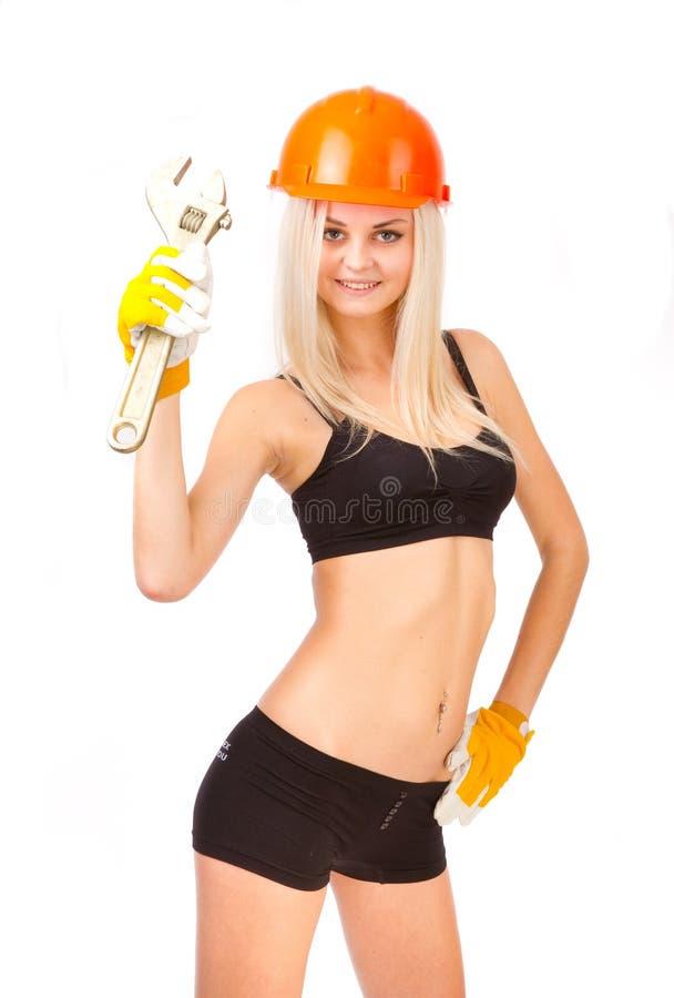 Härlig blondin med en skiftnyckel. fotografering för bildbyråer