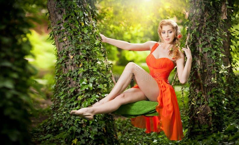 Härlig blondin med idérik frisyr på trädgårds- gunga royaltyfri foto