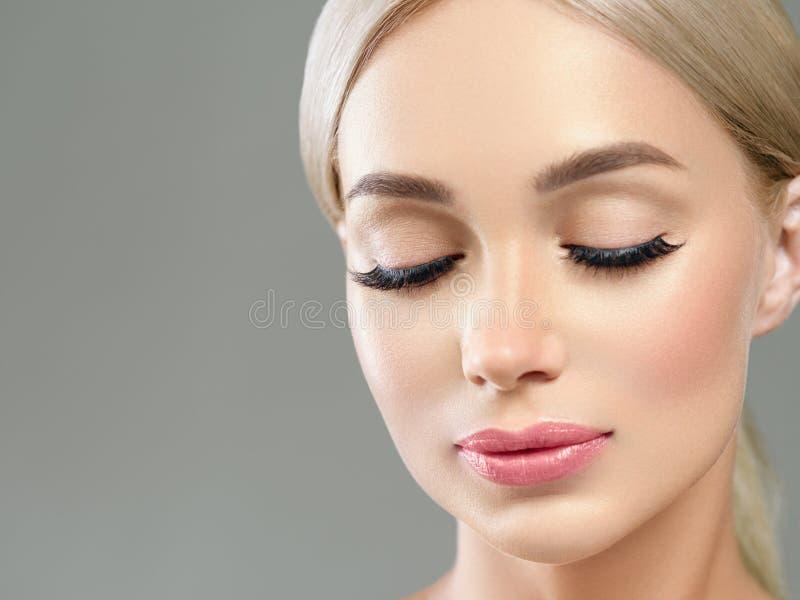 Härlig blondin med långa härliga ögonfrans och beautyful sund hud för blont hår och rosa kanter royaltyfri foto